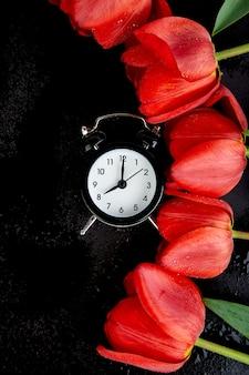 Despertador preto perto de tulipas vermelhas buquê