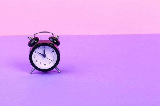 Despertador preto vintage em fundo lilás