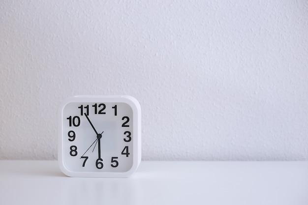 Despertador quadrado branco sobre uma mesa branca mostra seis horas
