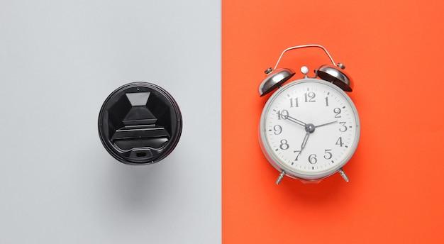 Despertador, recipiente com café na mesa cinza laranja. vista do topo