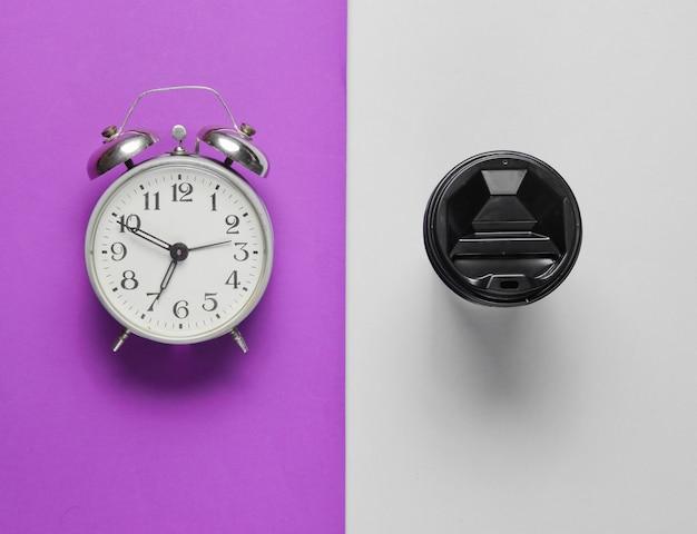 Despertador, recipiente com café na mesa cinza roxa. vista do topo