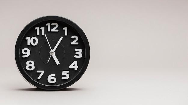 Despertador redondo preto contra um fundo cinza