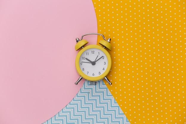 Despertador retrô amarelo em fundo de papel colorido criativo. minimalismo