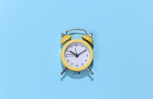 Despertador retro amarelo sobre fundo azul brilhante. . minimalismo