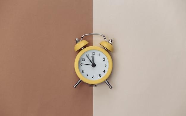 Despertador retrô amarelo sobre fundo bege marrom. . minimalismo