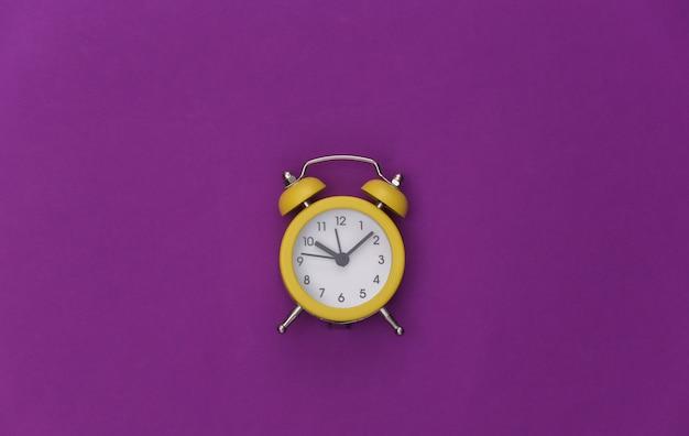 Despertador retrô amarelo sobre fundo roxo. . minimalismo