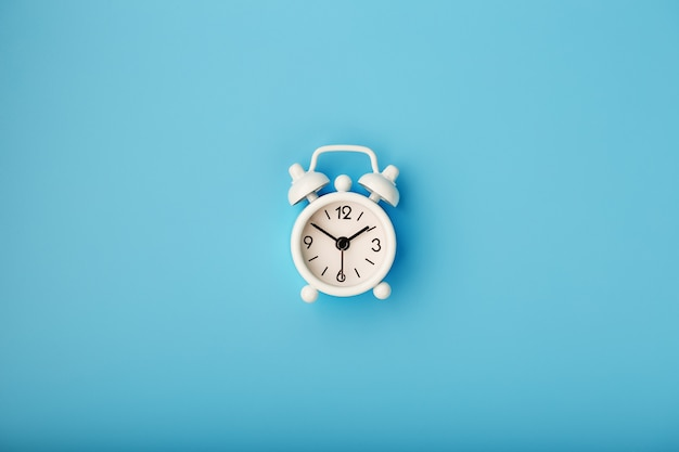 Despertador retrô branco sobre fundo azul. conceito de tempo com espaço livre para texto.