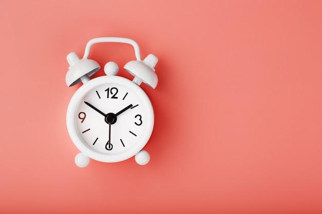Despertador retrô branco sobre fundo rosa. conceito de tempo com espaço livre para texto.