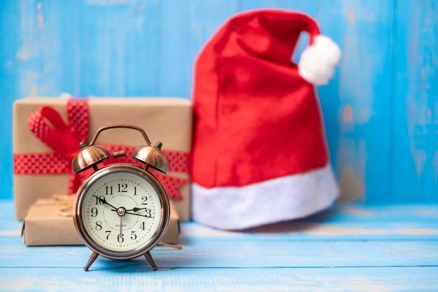 Despertador retrô com caixa de presente de natal feliz ou presente e chapéu de papai noel