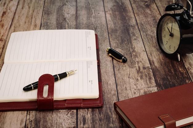 Despertador retrô com livro de memorando e caneta de luxo na mesa de madeira