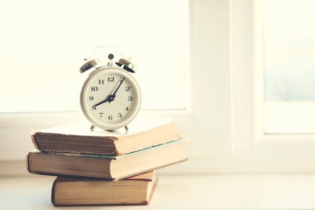 Despertador retrô com livros na janela