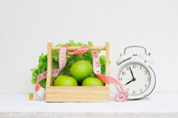 Despertador retro do vintage e maçãs e alface verdes na cesta de madeira na tabela de madeira branca do grunge.