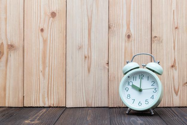Despertador retro do vintage na tabela de madeira, conceito do tempo.