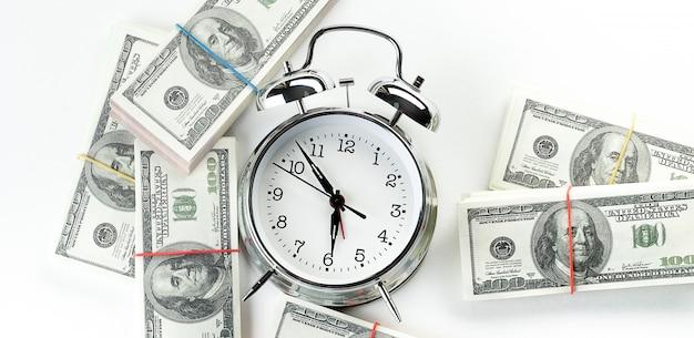 Despertador retrô e pilhas de notas de dólar