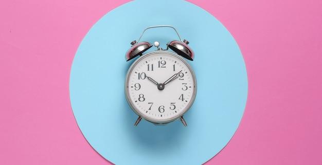 Despertador retrô em fundo rosa com círculo azul pastel. vista do topo