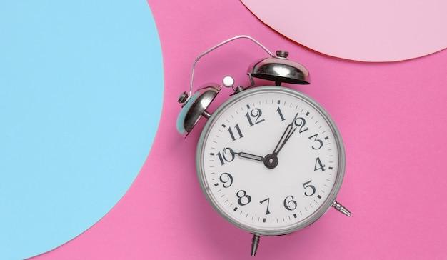 Despertador retrô em fundo rosa com círculos azuis pastel rosa para espaço de cópia. vista do topo