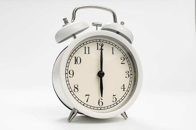Despertador retrô em um fundo branco. conceito de subidas de manhã cedo. tempo. primeiro turno na escola ou no trabalho.