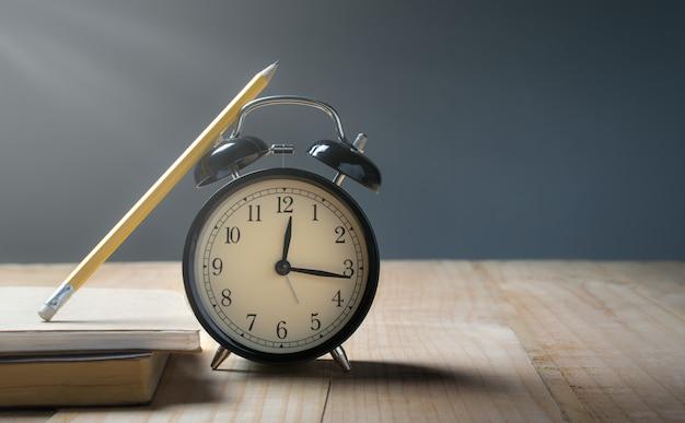 Despertador retro, lápis na tabela de madeira com tempo do fundo do grunge para o conceito do almoço.