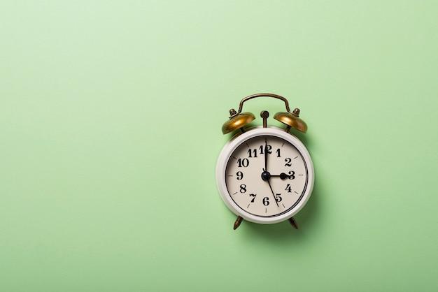 Despertador retro na superfície verde