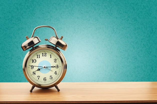Despertador retrô na velha mesa de madeira com fundo de parede verde menta
