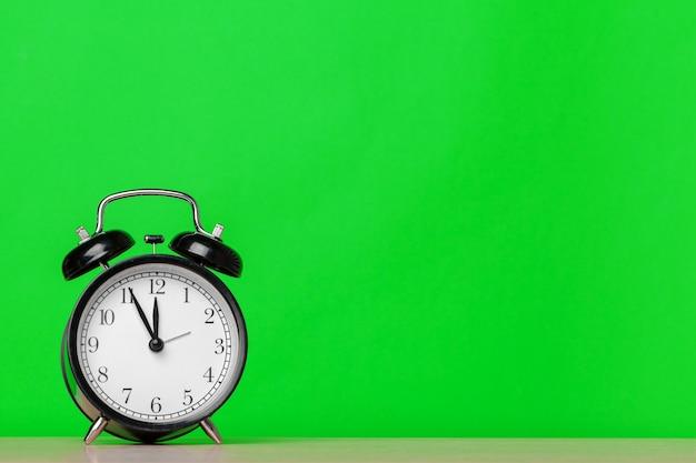 Despertador retrô no fundo da parede verde