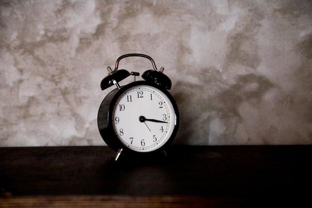 Despertador retro preto de gerenciamento de tempo alertando minutos após a hora da árvore no conceito de negócio com despertador antigo