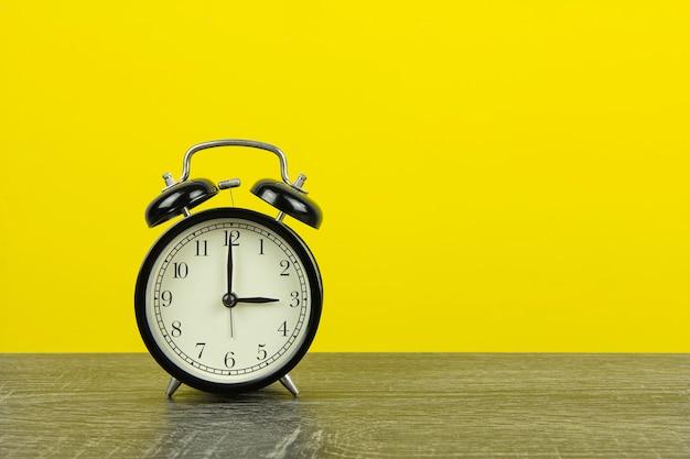 Despertador retrô preto na mesa de madeira e fundo amarelo.
