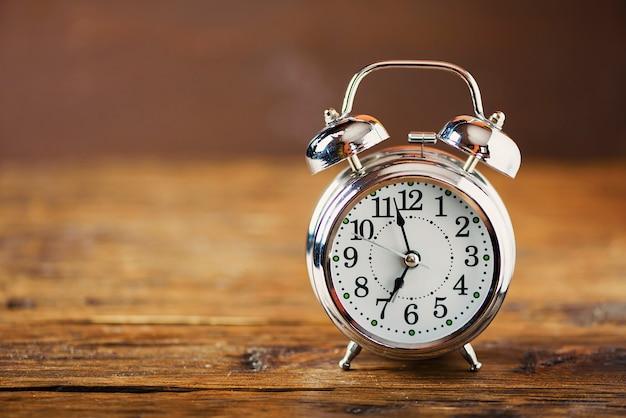 Despertador retro preto na placa de madeira, foco seletivo