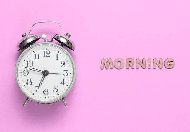Despertador retrô rosa com texto de manhã com letras.