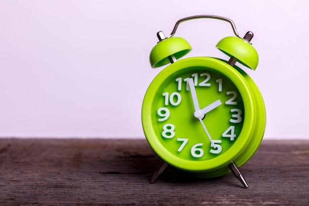 Despertador retro verde vintage na mesa de madeira, com espaço vazio para o seu texto. clássico com campainha dupla.