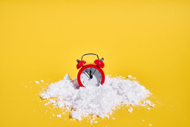 Despertador retrô vermelho com neve em fundo amarelo. conceito criativo de natal ou ano novo. . foto de alta qualidade