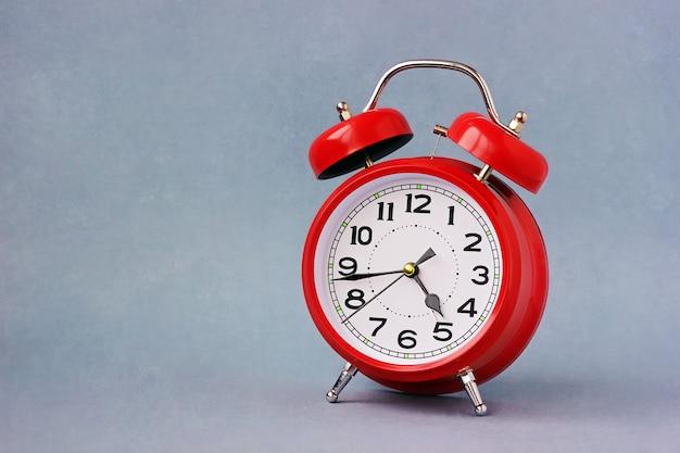 Despertador retro vermelho sobre em um fundo azul.
