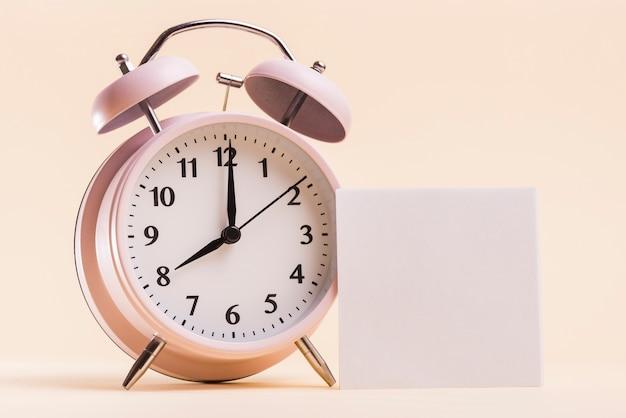 Despertador rosa com nota adesiva branca em branco sobre fundo bege