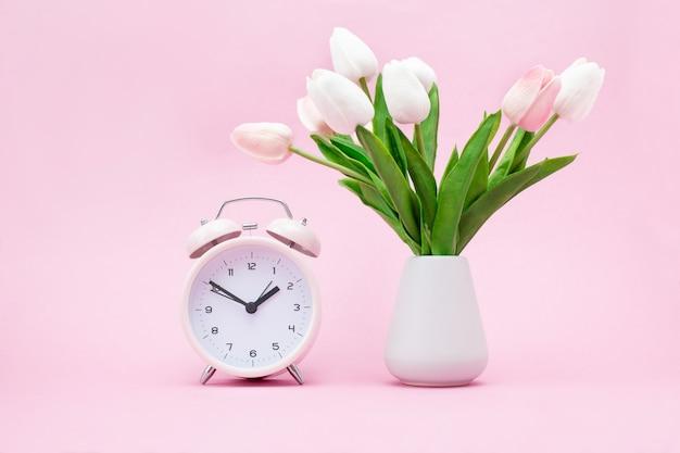 Despertador rosa e um buquê de flores em rosa