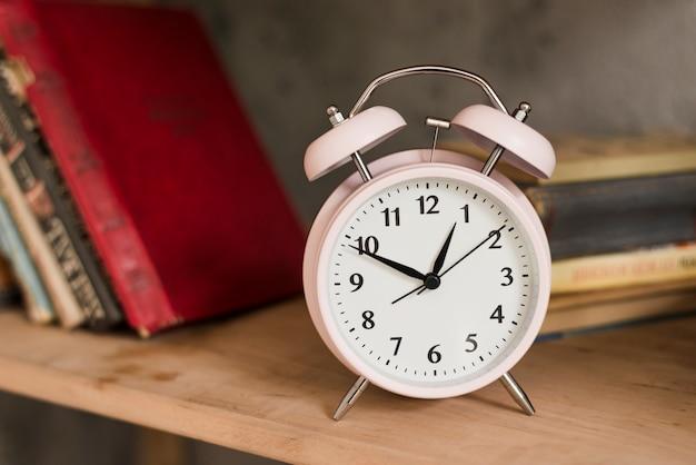 Despertador rosa na estante de madeira