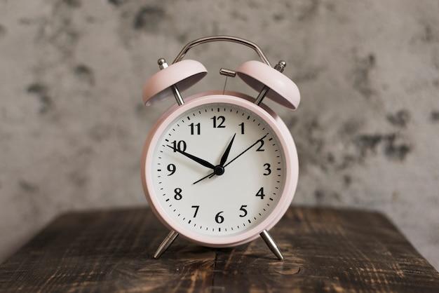 Despertador rosa na mesa de madeira contra a parede resistiu