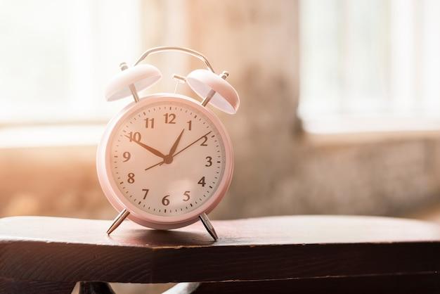 Despertador rosa na mesa de madeira na luz solar