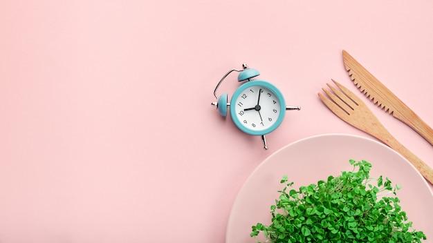 Despertador, talheres e prato com vegetação