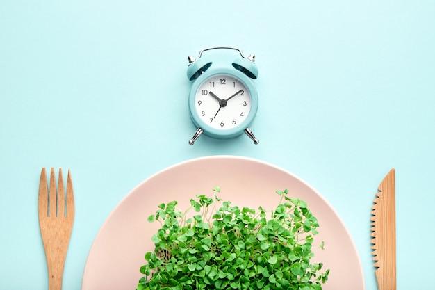 Despertador, talheres e prato rosa com folhas verdes. conceito de jejum, hora do almoço e dieta intermitente.