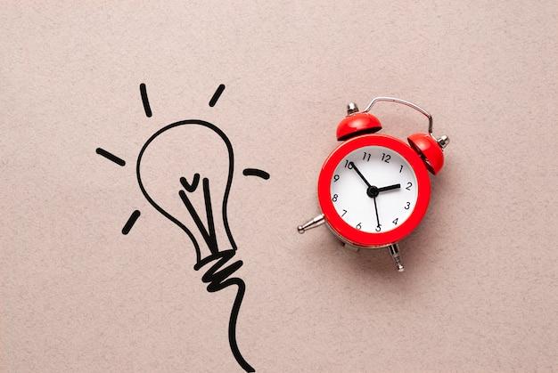 Despertador vermelho ao lado de um desenho de uma lâmpada