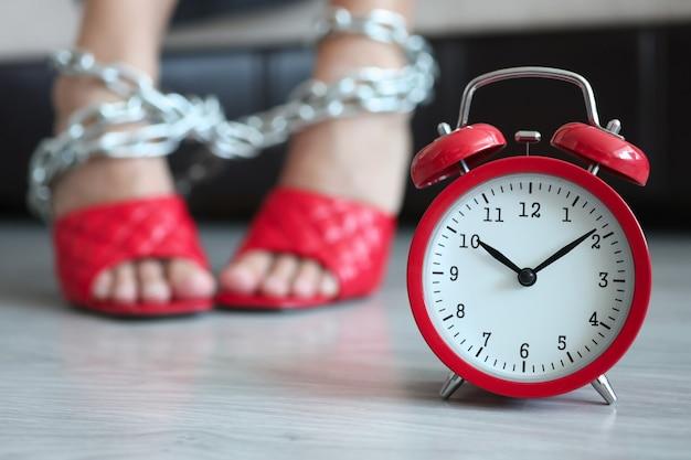 Despertador vermelho às dez da manhã com pernas femininas amarradas com corrente de despedida diariamente