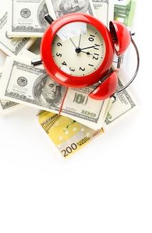 Despertador vermelho brilhante com uma pilha de notas de dólar e euro