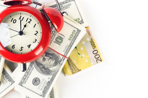 Despertador vermelho brilhante e pilhas de notas de dólar e euro