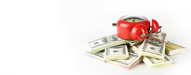 Despertador vermelho brilhante em estilo retro, sobre uma pilha de dólares e euros de papel. tempo é dinheiro. conceito de negócios.