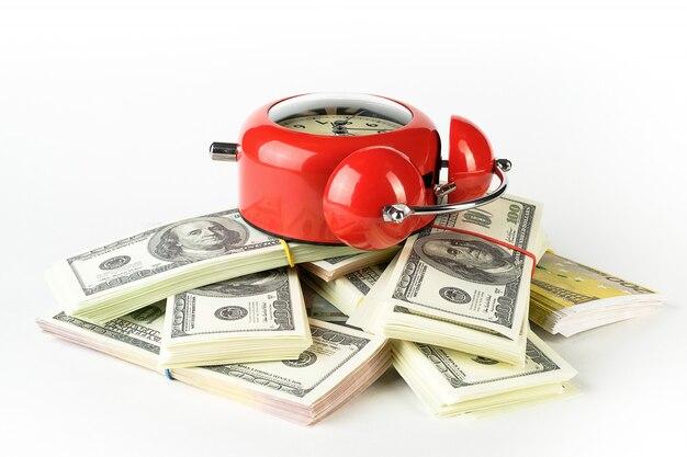 Despertador vermelho brilhante em estilo retro, sobre uma pilha de dólares e euros de papel.