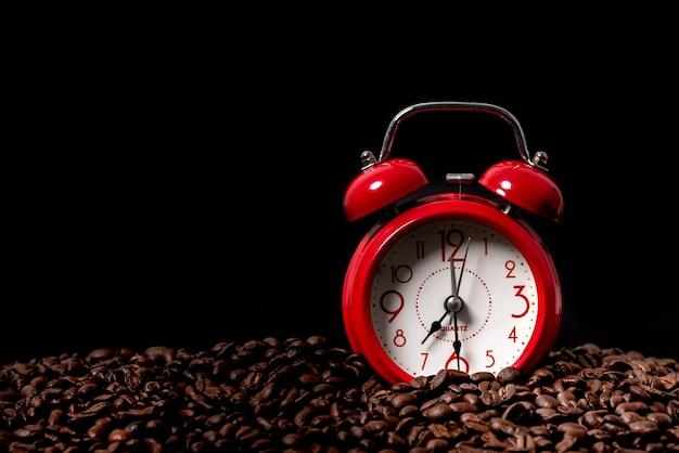 Despertador vermelho coloque em grãos de café torrados em fundo preto, ao tempo do conceito de bebida de café.