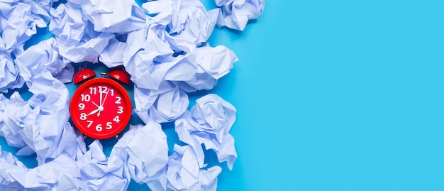 Despertador vermelho com bolas de papel amassado branco sobre um fundo azul.