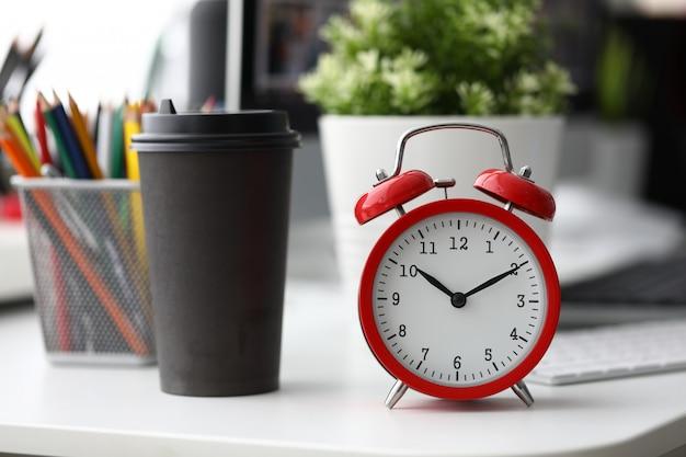Despertador vermelho com copo de café de papel preto