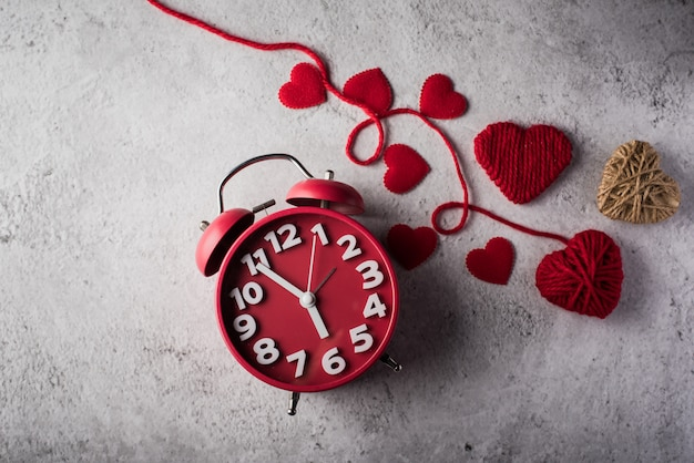 Despertador vermelho com coração vermelho, conceito de dia dos namorados.
