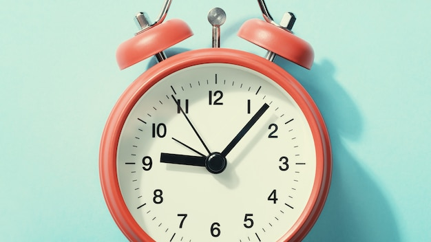 Despertador vermelho com sombra deitado no azul